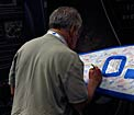 Attendee signing the IAU surfboard